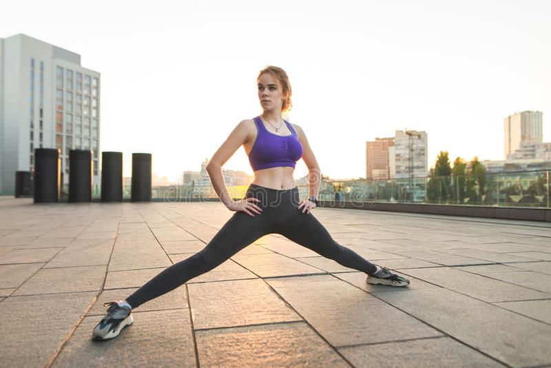 Street portrait of a girl in sportswear doing sports on the street and sunrise stock photography