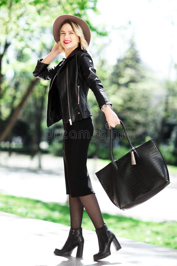 Street portrait of glamour sensual young stylish lady wearing trendy fall outfit. Blonde woman in black hat and leather. Jacket and bag. Back view stock photography