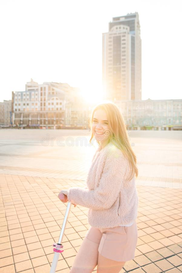 Street portrait of a happy girl, looking camera and laughing at the background of the sun royalty free stock image