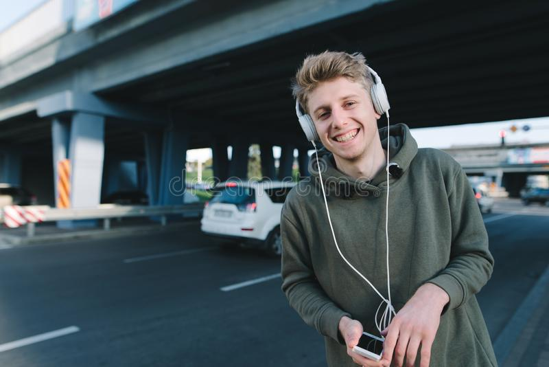 Street portrait of a happy young man who smiles, and listens to a musician in headphones in the background of urban architecture. stock photos