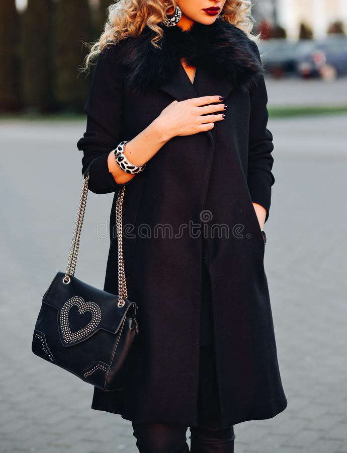 Street portrait shot of a beautiful young woman,dressed in black coat, on the shoulder fashion female bag, bracelets stock photo