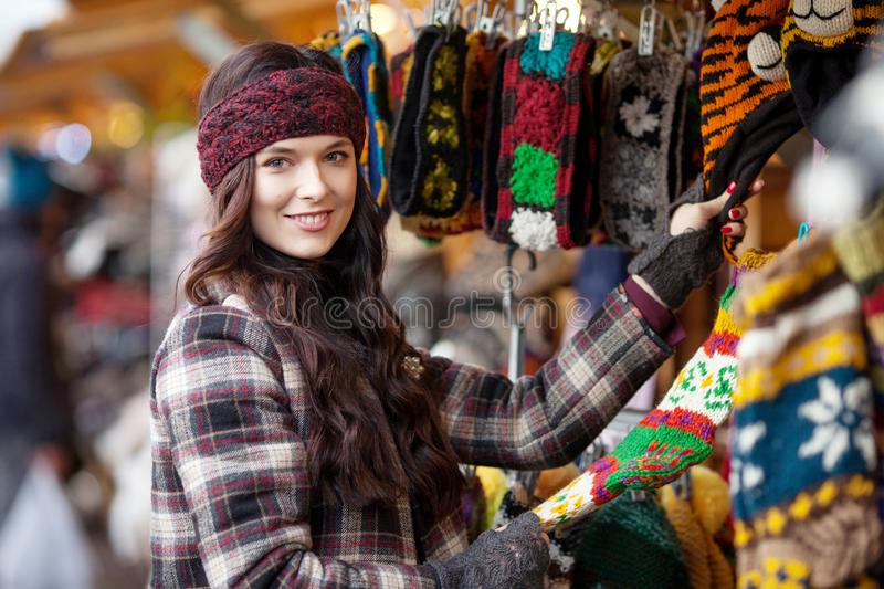 Street portrait of smiling beautiful young woman choosing warm knitted things on the festive Christmas fair. Travel, tourism,. Holidays and people concept royalty free stock photo