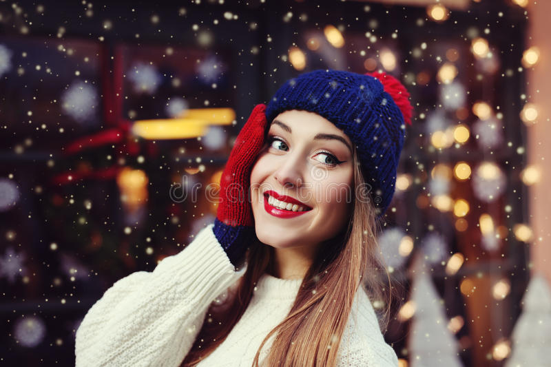 Street portrait of smiling beautiful young woman wearing classic winter knitted clothes. Model looking aside. Festive stock photo