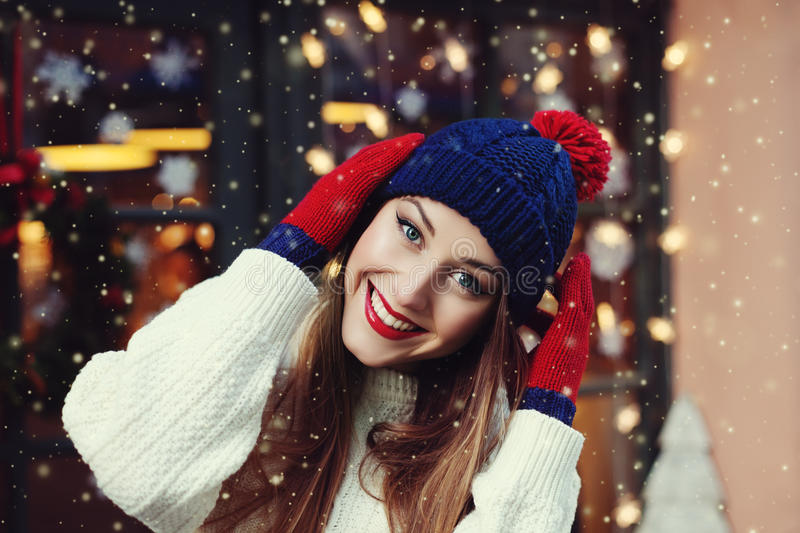 Street portrait of smiling beautiful young woman wearing classic winter knitted clothes. Model looking at camera stock photo