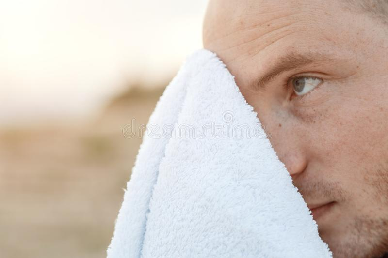 Street portrait of a sporty young Caucasian guy in a black t-shirt wipes his face with a towel.  stock photos