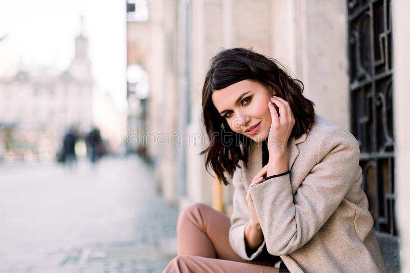 Street portrait of young beautiful happy smiling woman wearing stylish coat and pants. Model looking at camera. Female royalty free stock images