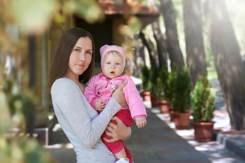 Street portrait of the young mother hugging her daughter with love stock image