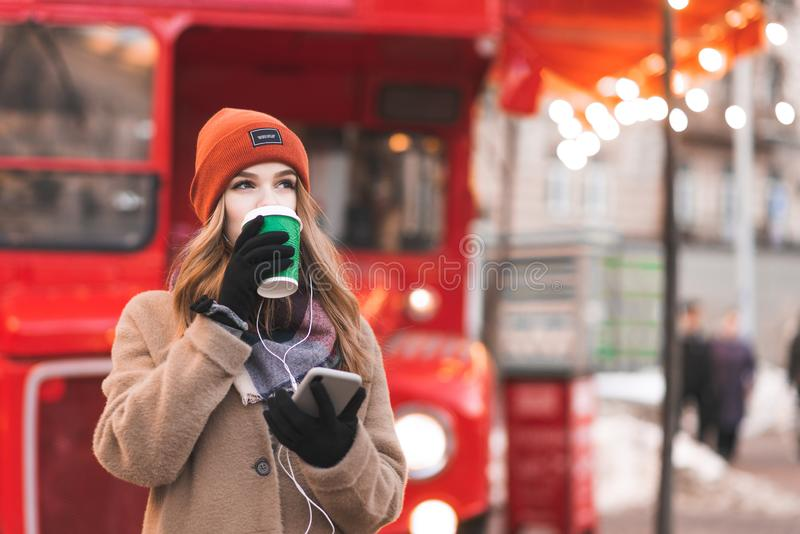 Street portrait of a young woman in warm clothes, standing on the background of a red bus with a smartphone in her hands stock photography