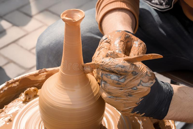 Street potter makes a vase of clay on a potter`s wheel. Close-up stock photography