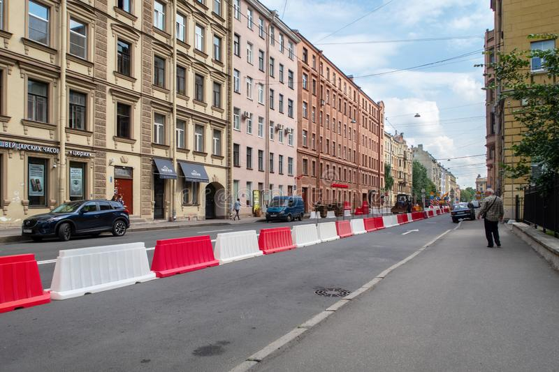 Street repair and road works in the city. white and red plastic barriers restricting car traffic on an asphalt street royalty free stock photography