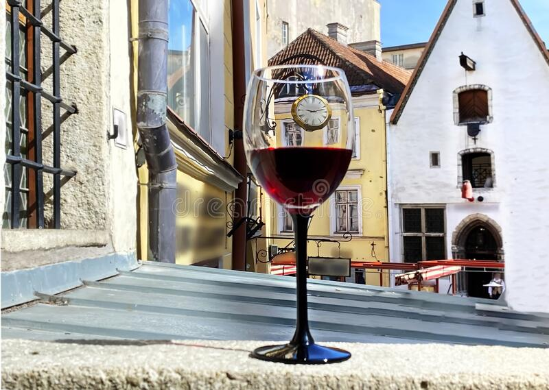 Street restaurant glass of red wine on table top street clock  urban medieval city lifestyle Tallinn old town  summer  travel to E. Stonia ,concept royalty free stock images