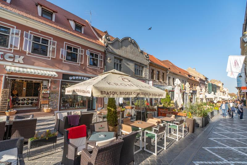 Street restaurant on the pedestrian street of old Brasov in Romania. One of the ten largest cities in Romania. Located in the heart of Romania, the city of stock photography