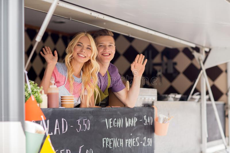 Happy young sellers waving hands at food truck. Street sale and people concept - happy young sellers waving hands and greeting at food truck royalty free stock photo