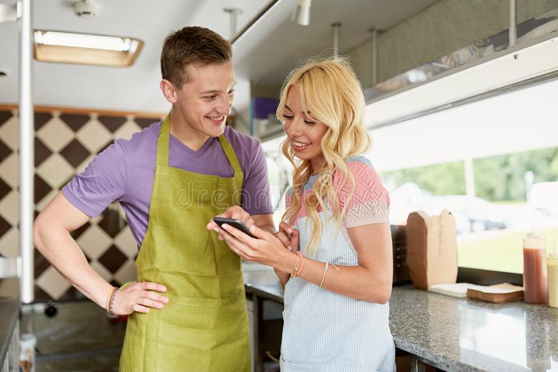 Couple of sellers with smartphone at food truck. Street sale, technology and people concept - happy couple of young sellers with smartphone at food truck stock image