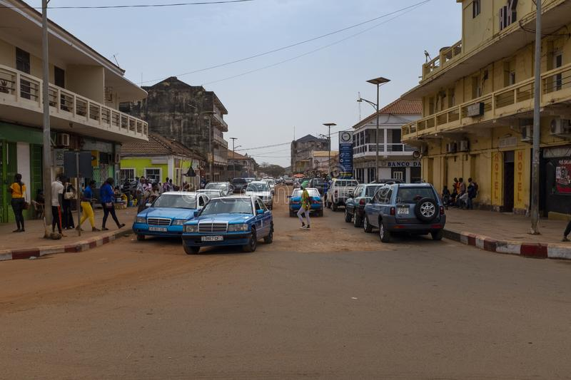 Street scene in the city of Bissau with old taxis and street vendors, in Guinea-Bissau, West Africa. Bissau, Republic of Guinea-Bissau - February 5, 2018: Street stock photo