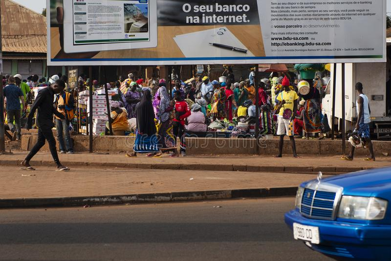Street scene in the city of Bissau with people at the Bandim Market, in Guinea-Bissau, West Africa. Bissau, Republic of Guinea-Bissau - January 31, 2018: Street stock image