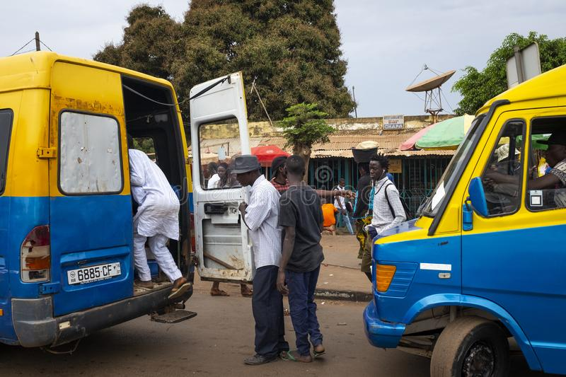 Street scene in the city of Bissau with people boarding a public bus Toca Toca at the Bandim Market, in Guinea-Bissa. Bissau, Republic of Guinea-Bissau royalty free stock images