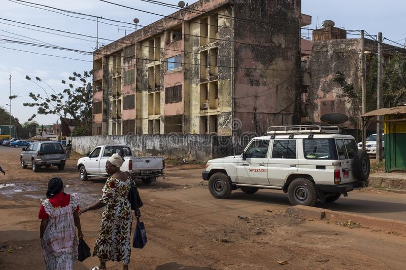 Street scene in the city of Bissau, with people and cars on a dirt road and residential buildings on the background, in Guinea-Bis. Bissau, Republic of Guinea stock photography