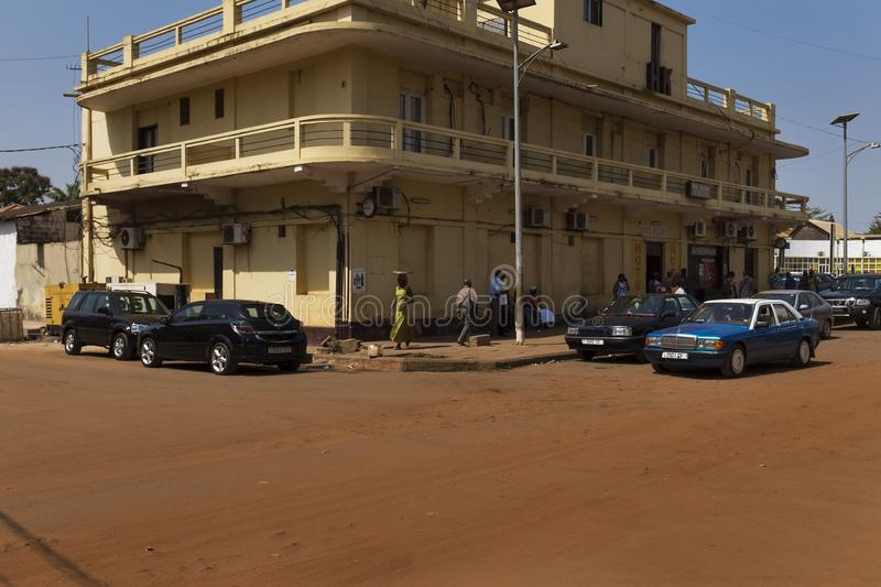 Street scene in the city of Bissau with people passing in front of an old hotel, in Guinea-Bissau. Bissau, Republic of Guinea-Bissau - January 30, 2018: Street stock photography