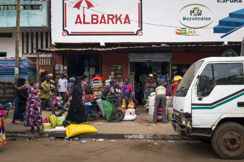 Street scene in the city of Bissau with people walking on a sidewalk and stores near the Bandim Market, in Guinea-Bissau. Bissau, Republic of Guinea-Bissau stock images