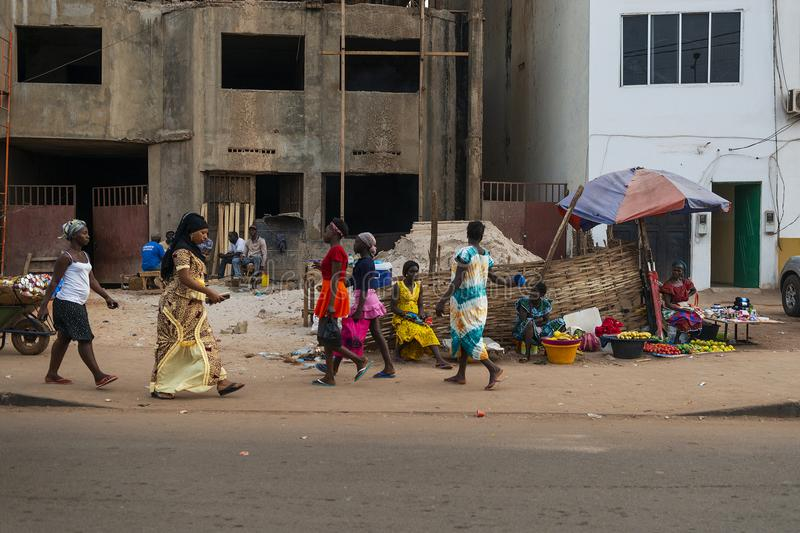 Street scene in the city of Bissau with people walking in a sidewalk and street vendors selling fruit, in Guinea-Bissau. Bissau, Republic of Guinea-Bissau royalty free stock photography