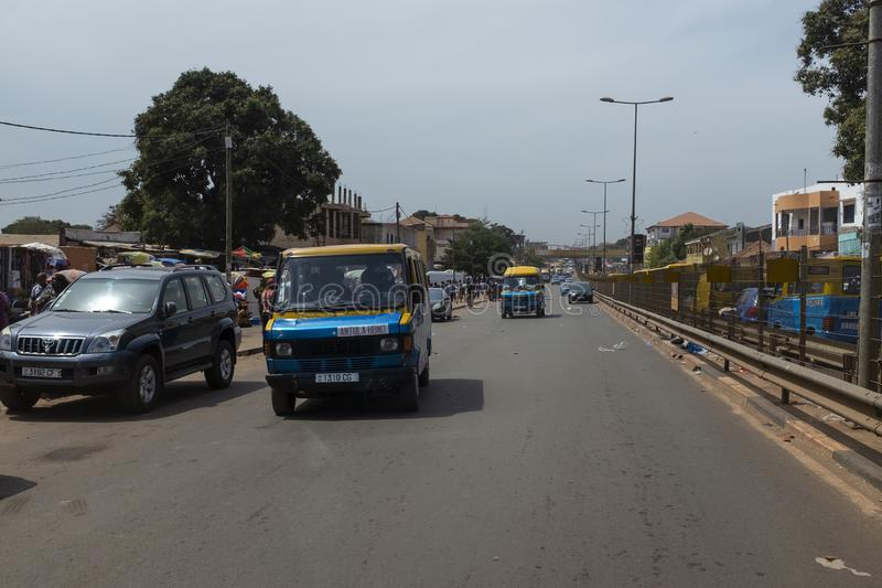 Street scene in the city of Bissau with public buses Toca Toca in an avenue near the Bandim Market, in Guinea-Bissau. Bissau, Republic of Guinea-Bissau stock image