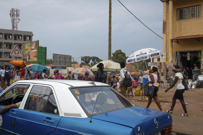 Street scene in the city of Bissau with a taxi and people walking on a sidewalk near a street market, in Guinea-Bissau. Bissau, Republic of Guinea-Bissau stock image