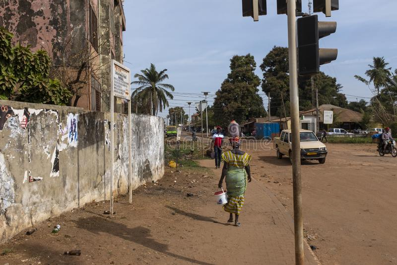 Street scene in the city of Bissau, with a woman carrying a plastic container on her head, in Guinea-Bissau stock photos