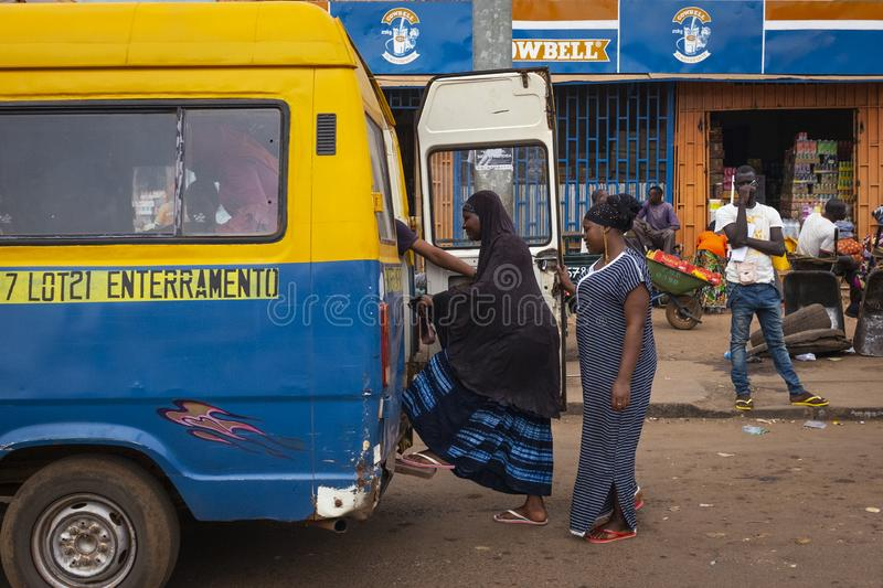 Street scene in the city of Bissau with women boarding a public bus Toca Toca at the Bandim Market, in Guinea-Bissau. Bissau, Republic of Guinea-Bissau stock image