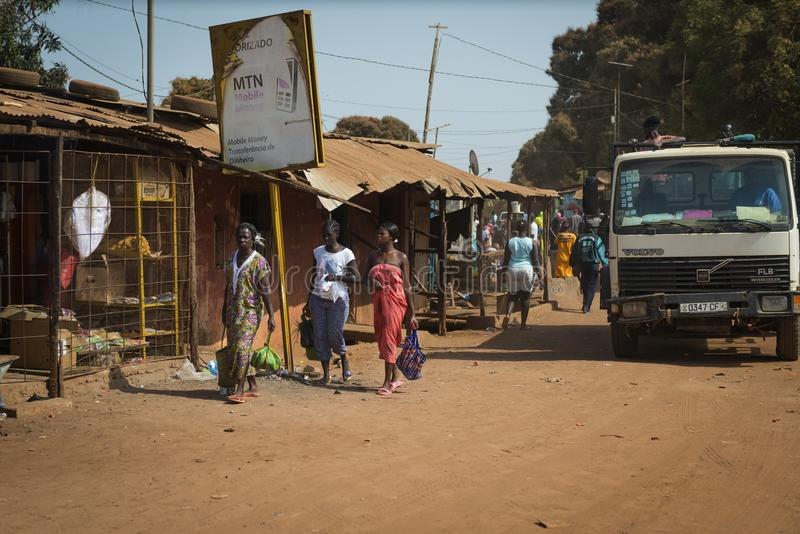 Street scene in the city of Bissau with women waling along a dirt road, in Guinea-Bissau. Bissau, Republic of Guinea-Bissau - January 29, 2018: Street scene in stock image