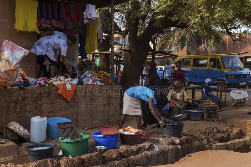 Street scene in the city of Bissau with women washing clothes in front of their home. Bissau, Republic of Guinea-Bissau - February 7, 2018: Street scene in the stock photos
