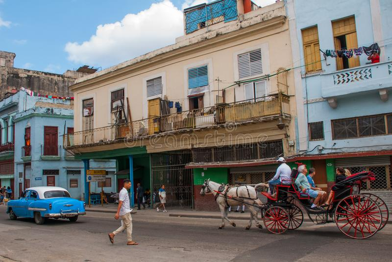 Street scene with classic old cars and traditional colorful buildings in downtown Havana. Cuba royalty free stock images