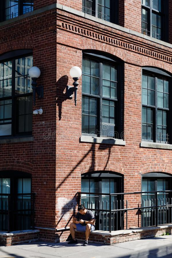Street scene in Dumbo, Brooklyn. NEW YORK, USA - Sep 22, 2017: Street scene in Dumbo, Brooklyn. A young man with a mobile phone sits on the parapet of a brick royalty free stock photo