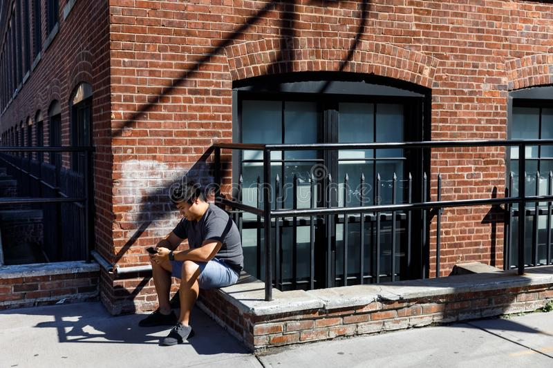 Street scene in Dumbo, Brooklyn. NEW YORK, USA - Sep 22, 2017: Street scene in Dumbo, Brooklyn. A young man with a mobile phone sits on the parapet of a brick royalty free stock images