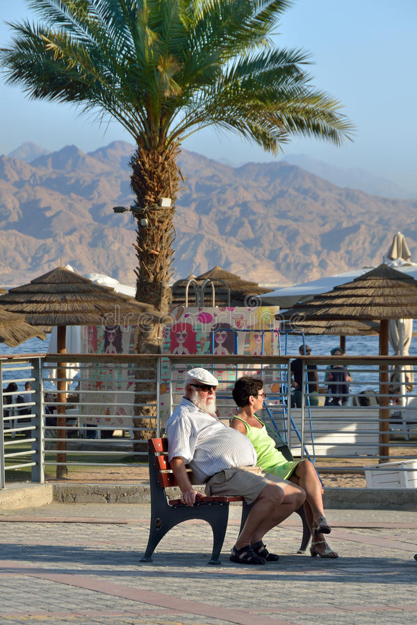 Street scene in Eilat, Israel. EILAT, ISRAEL - MARCH 31, 2015: Unidentified senior couple relaxing on the bench in Eilat at sunset. This is one of the popular royalty free stock image