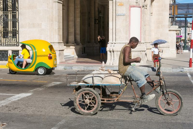 Street scene in Havana. Bicycle carrier and Coco taxi parked in stock photography