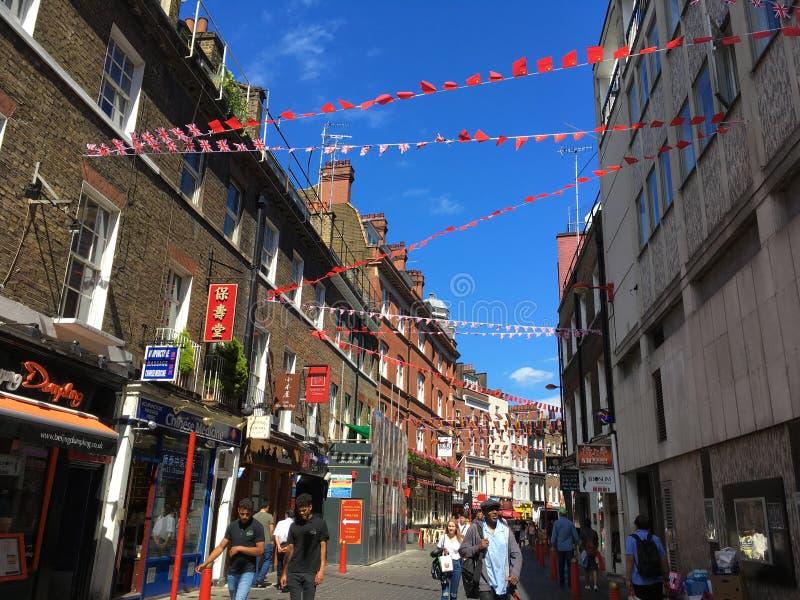 Street scene, Lisle Street, Chinatown, London, England. Street scene in summer, with people walking, decorated with bunting, Lisle Street, Chinatown, London royalty free stock photography