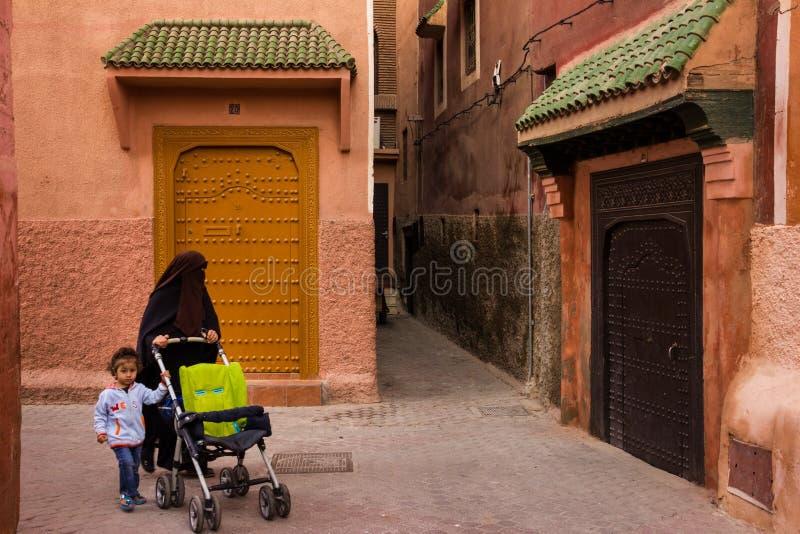 Street scene. Marrakesh. Morocco. Street scene in the medina. woman wearing burka pushing a stroller. Marrakesh. Morocco stock photos