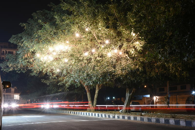 Street Scene at night in a urban town, light trails of car lights, decoration festive lighting on trees royalty free stock photo