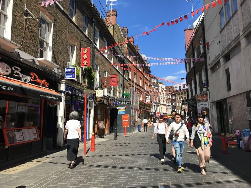 Street scene, Lisle Street, Chinatown, London, England. Street scene in summer, with people walking, decorated with bunting, Lisle Street, Chinatown, London stock image