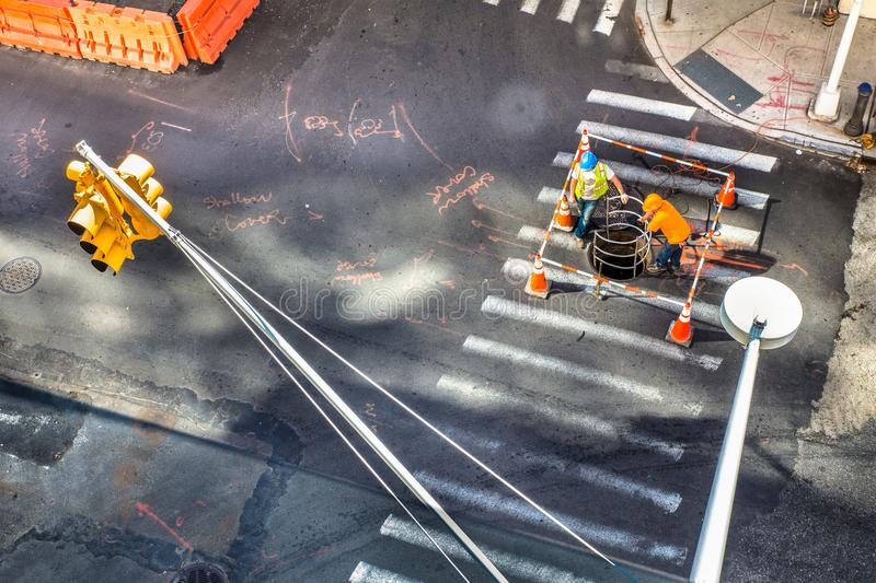 Street scene with utility workers. Industrial scene from above of non recognizable utility workers and urban intersection royalty free stock image