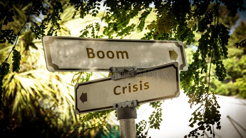 Street Sign Boom versus Crisis. Street Sign the Direction Way to Boom versus Crisis royalty free stock photo