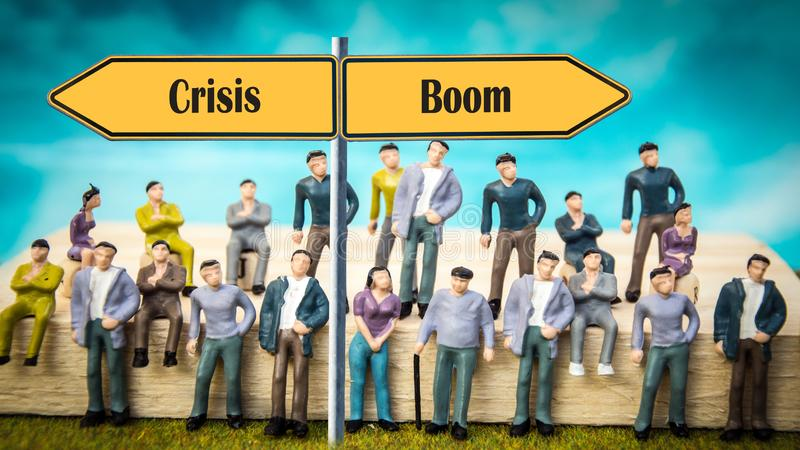 Street Sign Boom versus Crisis. Street Sign the Direction Way to Boom versus Crisis stock photo