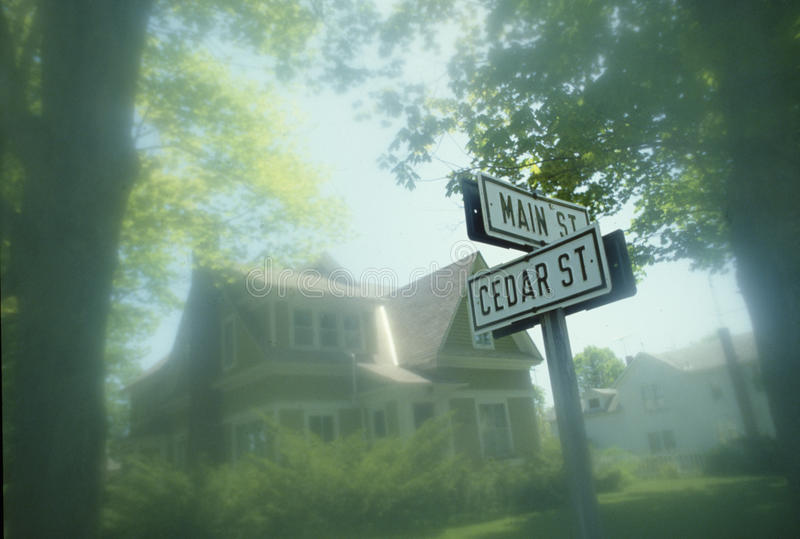 Street sign at corner of Main and Cedar with Victorian house in background, Michigan stock images
