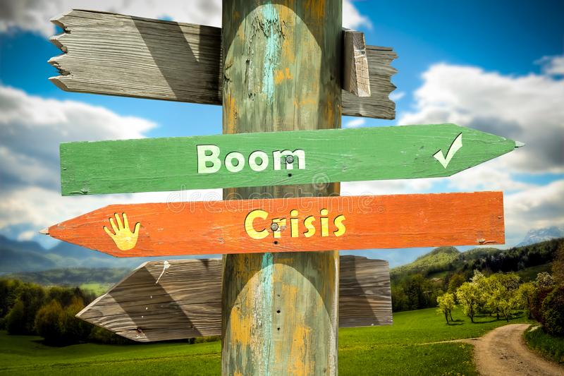 Street Sign Boom versus Crisis. Street Sign the Direction Way to Boom versus Crisis stock photos