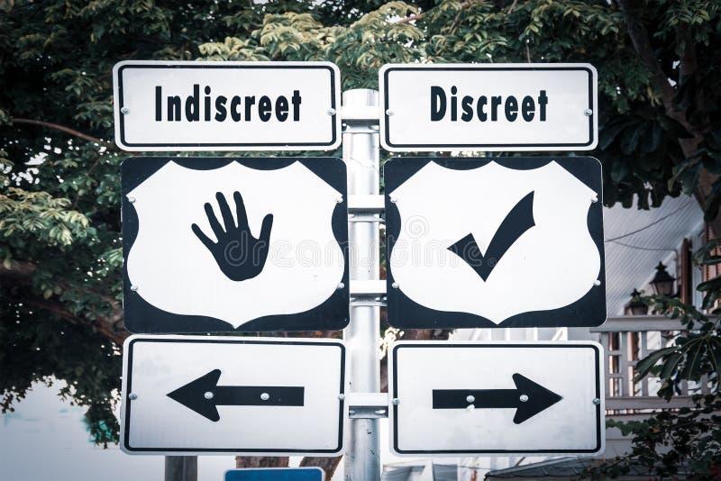 Street Sign Discreet versus Indiscreet. Street Sign the Direction Way to Discreet versus Indiscreet royalty free stock photos