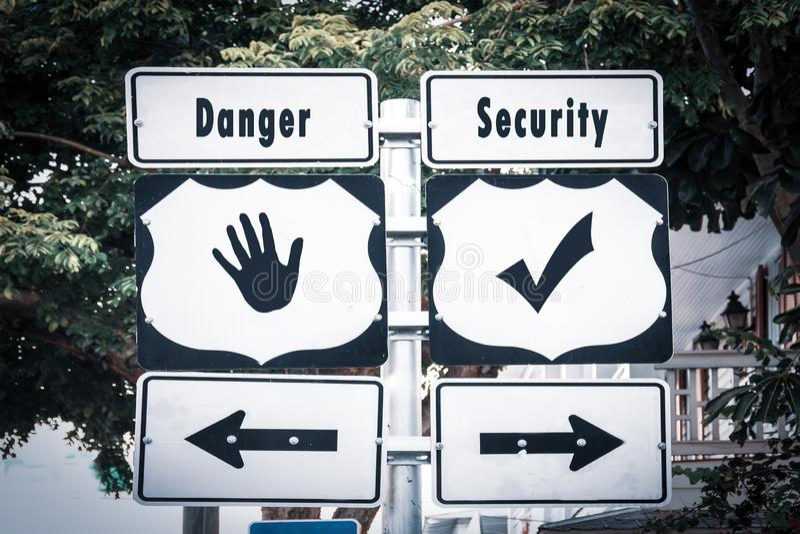 Street Sign to Security versus Danger. Street Sign the Direction Way to Security versus Danger stock photos