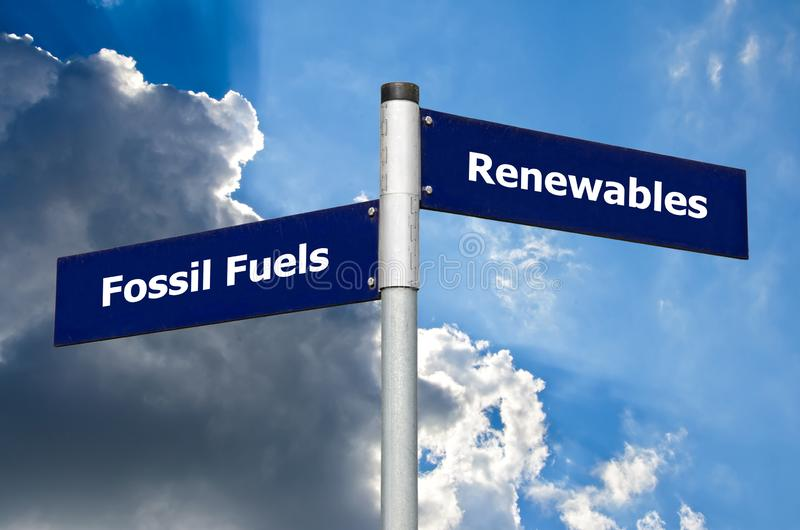 Street sign in front of cloudy sky representing choice between 'fossil fuels' and 'renewables`. Street sign in front of cloudy sky representing choice royalty free stock photo