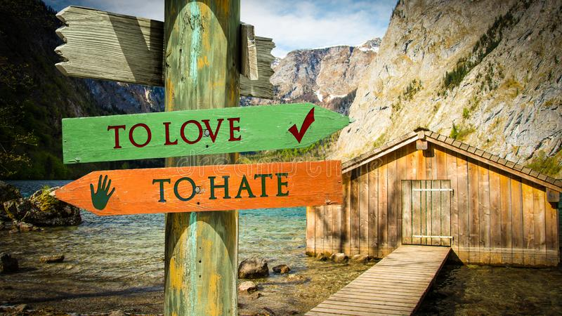 Street Sign LOVE versus TO HATE. Street Sign TO LOVE versus TO HATE stock photos