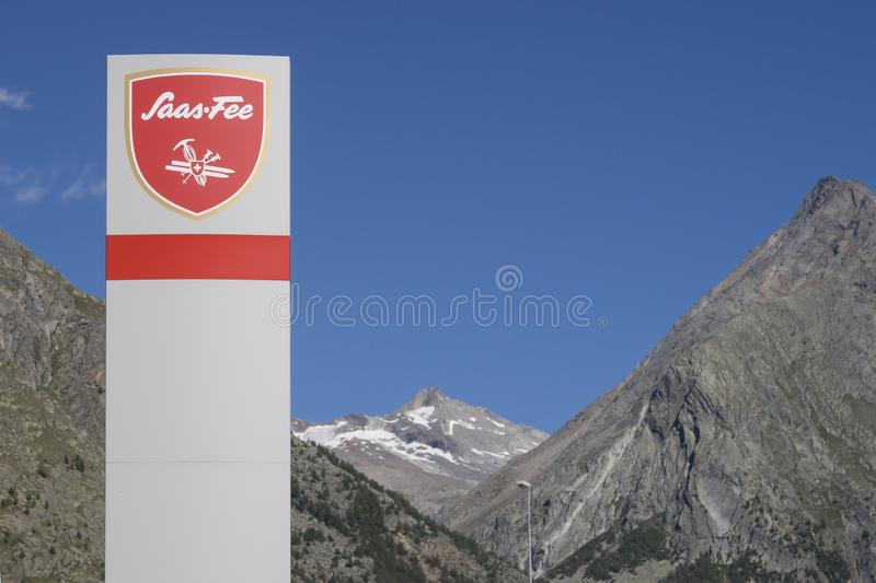 Street sign with the name Saas-Fee on it, a wintersports city in Switzerland with mountains and a blue sky on the royalty free stock photography